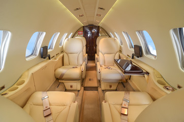 Luxury interior of genuine leather in the modern business jet and sunlight at the window