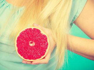 Woman holding red grapefruit