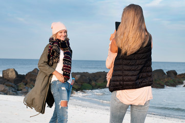 Friends. Girls take picture on the beach