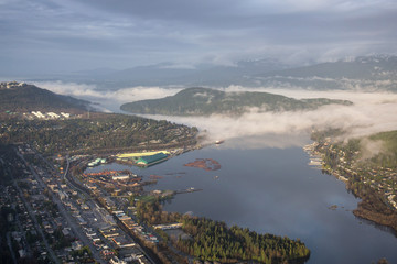 Aerial View of Port Moody, Greater Vancouver, British Columbia, Canada. Taken during a cloudy sunrise with fog patches.