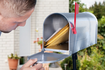 Man opening his mailbox to remove mail