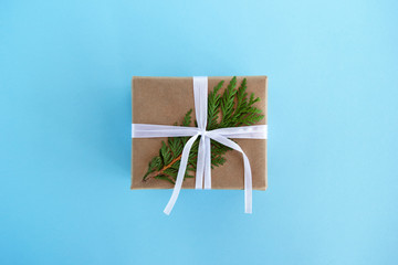Gift box wrapped of craft paper, white ribbon and decorated fir branch on the blue background, top view. Christmas present.