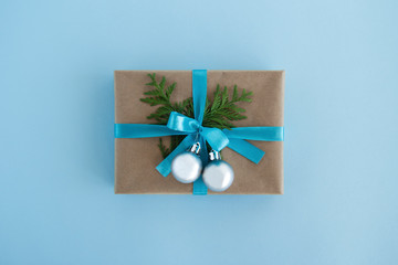 Gift box wrapped of craft paper, blue ribbon and decorated fir branches and silver Christmas balls on the blue background, top view. Christmas present.