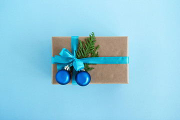 Gift box wrapped of craft paper, blue ribbon and decorated fir branches and blue Christmas balls on the blue background, top view. Christmas present.