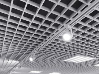 row of bright halogen spotlights on exhibition ceiling grid