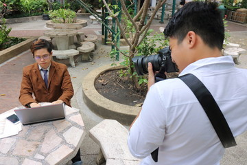 Photographer takes a photo of portrait of handsome young business man while using laptop.