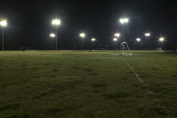 Empty athletic soccer fields at night with lights on