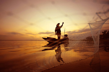 Fisherman is fishing on the boat by using net at sea while sunset.