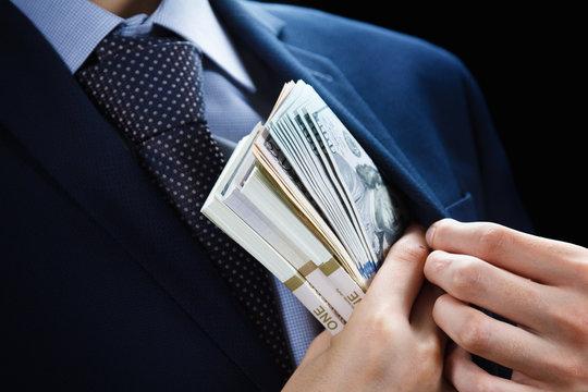 Concept for corruption, finance profit, bail, crime, bribing, fraud. Bundle of dollar cash in hand.