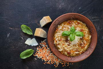 Italian soup with lentils and pasta on a dark brown scratched metal background, above view