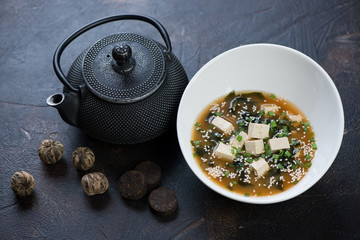 White bowl with miso soup, asian teapot and green tea balls, selective focus