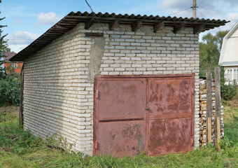 A rural no name self-made barn for storing firewood and tools is made of white silicate bricks.