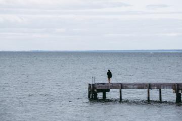 海の桟橋に立っている女性