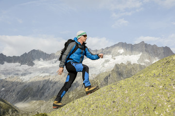 A sporty alpinist climbs a mountain summit in the Swiss Alps
