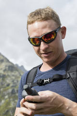 Alpinist is oriented with a GPS device in the terrain