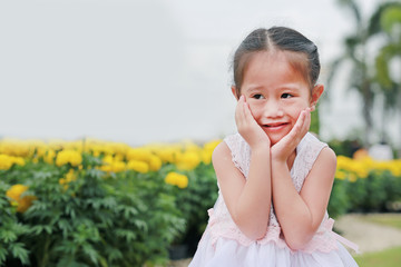 Smiling little asian girl pose touching cheek and looking camera in the nature park.