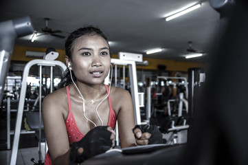 sexy and sweaty Asian woman training hard at gym using elliptical pedaling machine gear in intense workout
