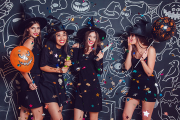 Beautiful girls in witches costumes blow up confetti on a dark background with a picture. Halloween.