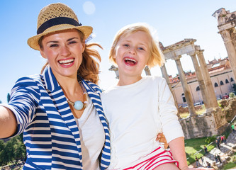 mother and child travellers against Roman Forum taking selfie