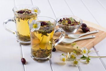 Herbal tea ingredients with hip roses, chamomile, herbs on white wooden table