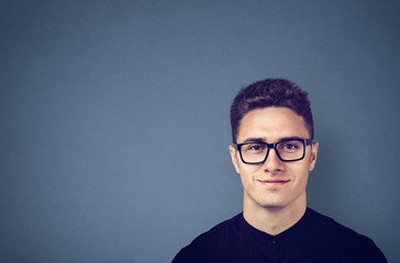 Happy young man with glasses, smiling