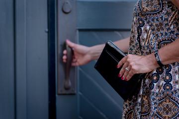 woman holding black wallet with hand on door handle