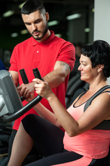Personal coach with female client in gym.