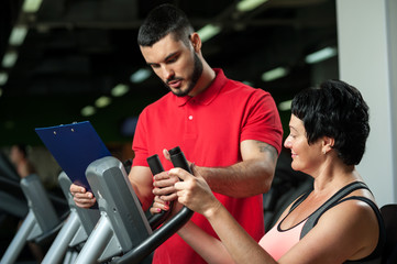 Middle aged woman working out with coach in gym