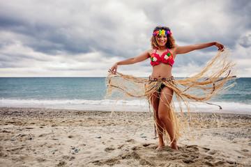 Beautiful and happy hawaiian woman portrait dancing on the beach
