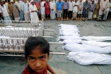 Men prepare for prayer behind bodies of Rohingya refugees who died after boat capsizing, near Cox's Bazar