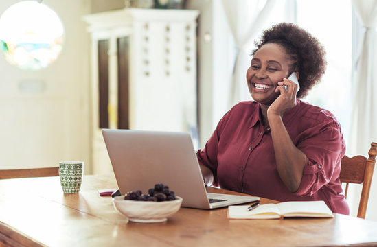Smiling African woman talking on her cellphone and working online