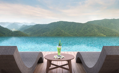 Swimming pool terrace with mountain view 3d rendering image.Furnished with rattan and wooden furniture. There are surrounding with nature and mountain