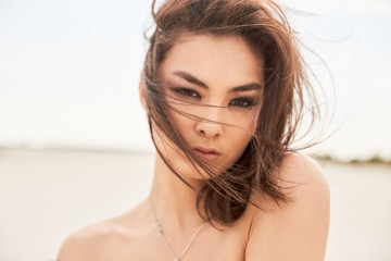 A closeup portrait of an asian girl topless on a beach in backlight