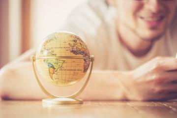 Junger Mann plant Weltreise, Globus und Landkarte