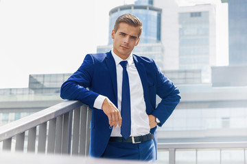 Handsome man in a blue suit against a city background on a sunny day