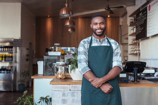 Smiling African entrepreneur standing at the counter of his cafe