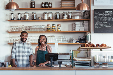 Two smiling young African entrepreneurs standing at their bakery counter