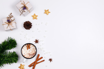 Winter christmas holiday background. Cup of hot chocolate drink with marshmallows, cinnamon sticks, anise star, gift box and golden ornaments on white background.