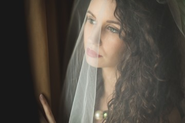 Thoughtful bride looking through window