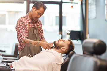 Professional barber cutting a beard of a handsome man