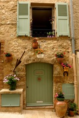 Picturesque stone facade with flowering plants medieval village of Valbonne, Provence, France