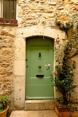 Charming stone doorway with climbing roses in medieval village of Valbonne, Provence, France