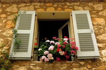 geraniums in window in medieval village of Gourdon, Provence, France