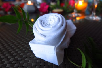 white napkin folded into shape of rose on candlelit table with flowers