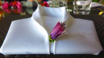 White napkin folded into shape of tuxedo shirt with flower