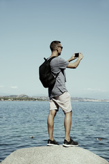 man taking a photo of the sea in Sardinia, Italy
