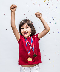 Successful beautiful child laughing with champion medals, celebrating over confettis