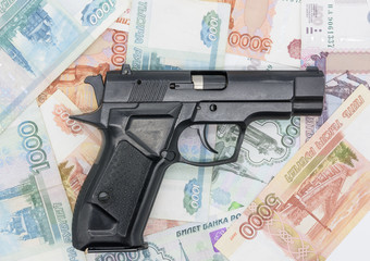 The black gun lies on the money with the barrel to the right