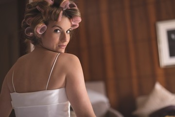 Beautiful bride with hair curlers on her head at home