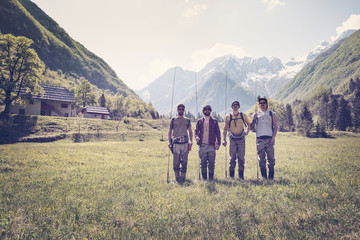 Slovenia, Bovec, four anglers standing on meadow near Soca river